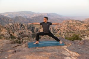 A man practising yoga in front of a mountainous backdrop