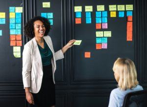 Woman giving presentation using a blackboard and post-it notes for note taking.