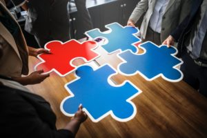 Group of people working as a team to connect puzzle pieces