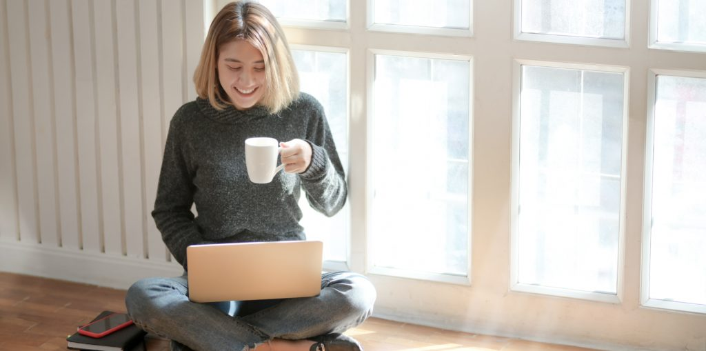 woman watches webinar on laptop whilst drinking coffee
